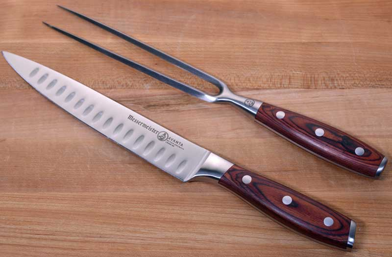 Messermeister Avanta Pakkawood 2-Piece Kullenschliff Carving Set with Knife and Fork on a wooden cutting board.