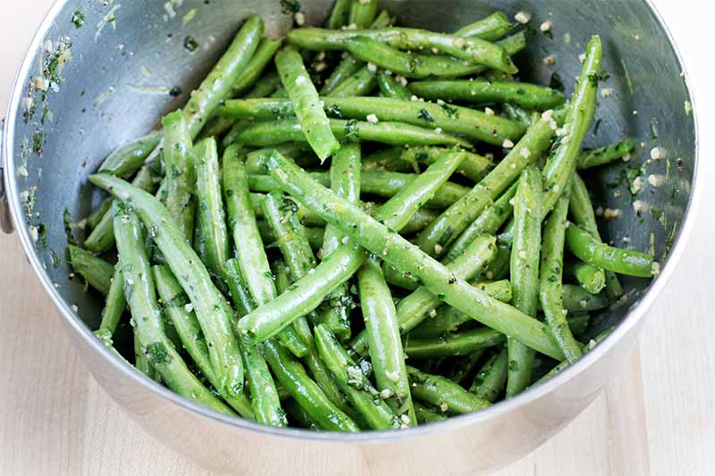 A stainless steel mixing bowl full of string beans tossed in a mixture of lemon juice, minced garlic, and chopped herbs.