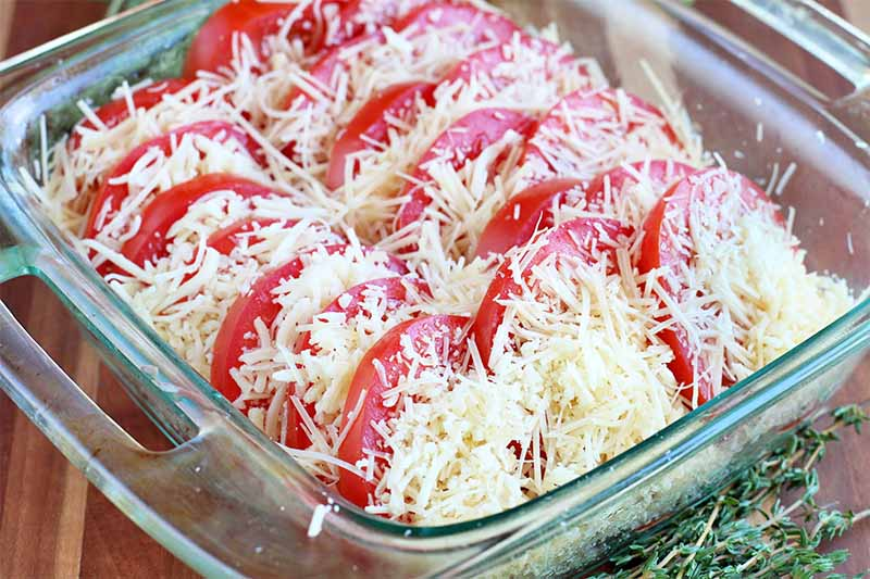 Oblique view of layered tomato slices and shredded Italian cheese in a square glass baking dish, on a brown tabletop with sprigs of fresh thyme.