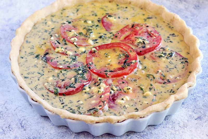 An egg, herbs, and tomato mixture fills a pie shell in a white ceramic tart pan, on a white and blue-gray speckled surface.