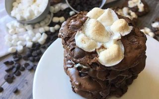 Horizontal image of chocolate cookies with marshmallows on a white plate.
