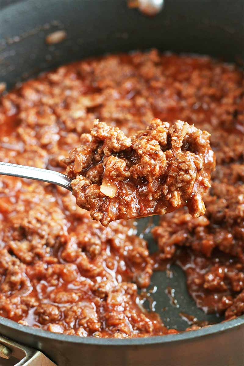 A large spoonful of ground beef with a red sauce is being held up to the camera, with a large stainless steel frying pan containing more of the mixture in the background.