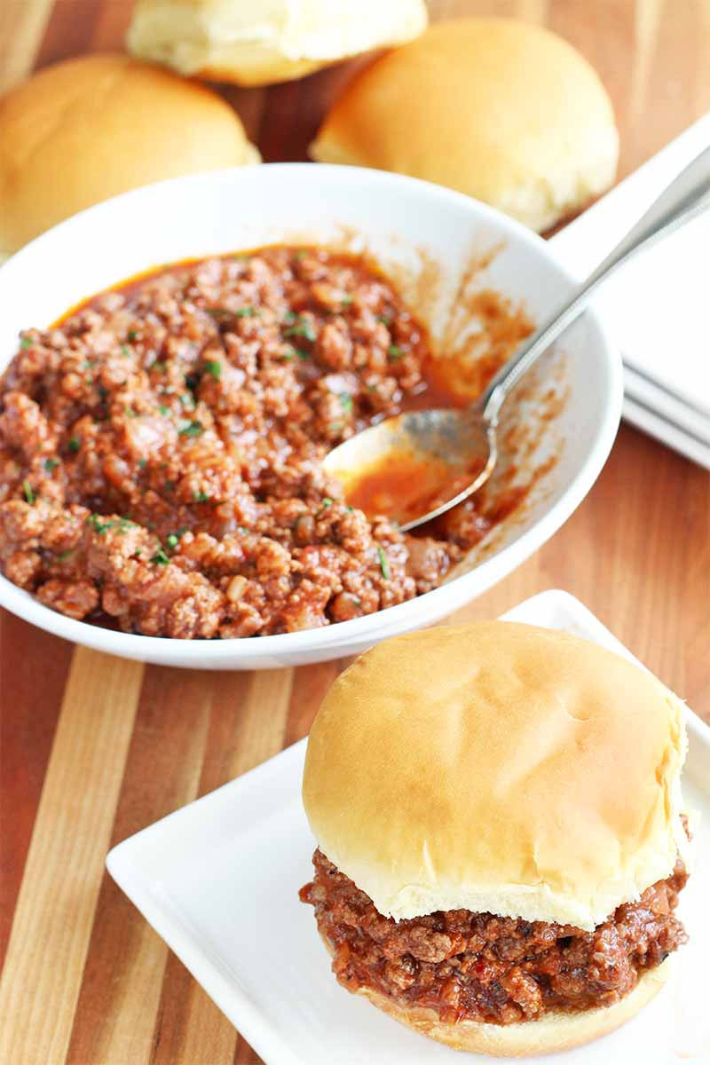 A large white bowl of beef sloppy joe with a stainless steel serving spoon, beside a small stack of square white plates, with a serving on a hamburger bun in the foreground, on a brown wood table.