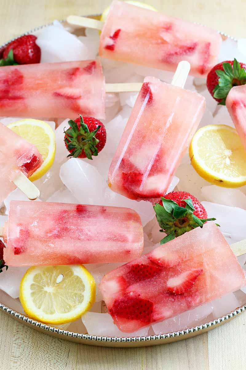 Pink strawberry lemonade popsicles on a silver tray of ice, sliced lemons, and whole berries, on a wood background.
