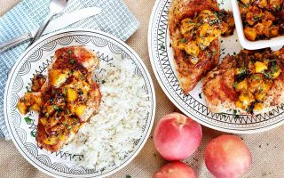 Top-down shot of two plates of chicken with white rice and chipotle fruit sauce, with three whole peaches, silverware, and a folded cloth napkin.