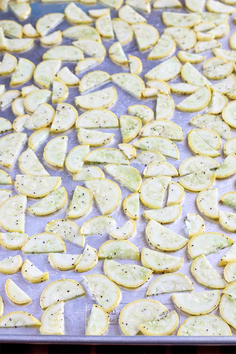 Vertical oblique image of thinly sliced yellow summer squash sprinkled with salt and pepper, on a silver baking sheet.