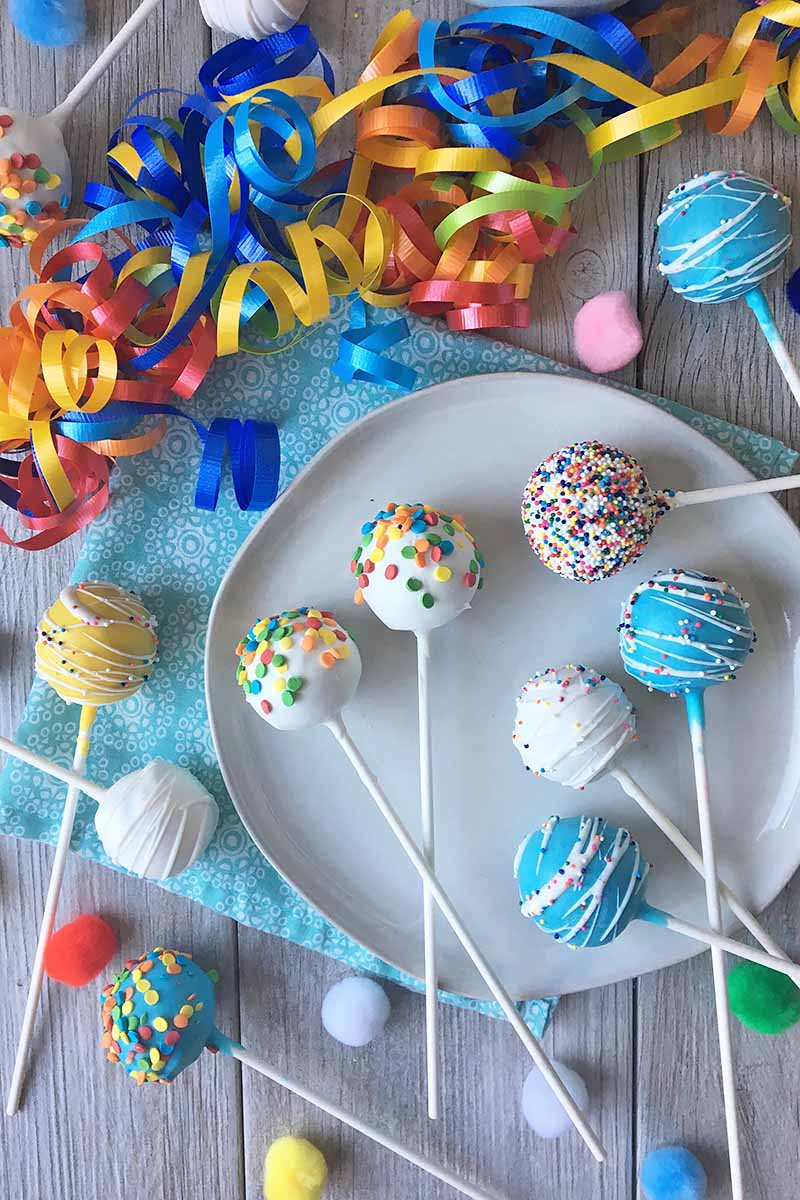 Vertical top-down image of assorted treats on sticks surrounded by streamers.