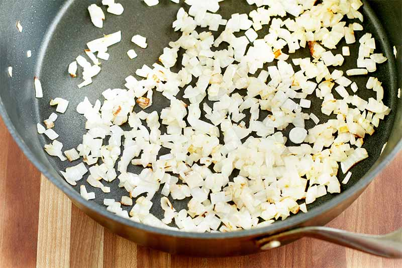 Sauteed chopped onions in a nonstick frying pan, on a brown wood surface.
