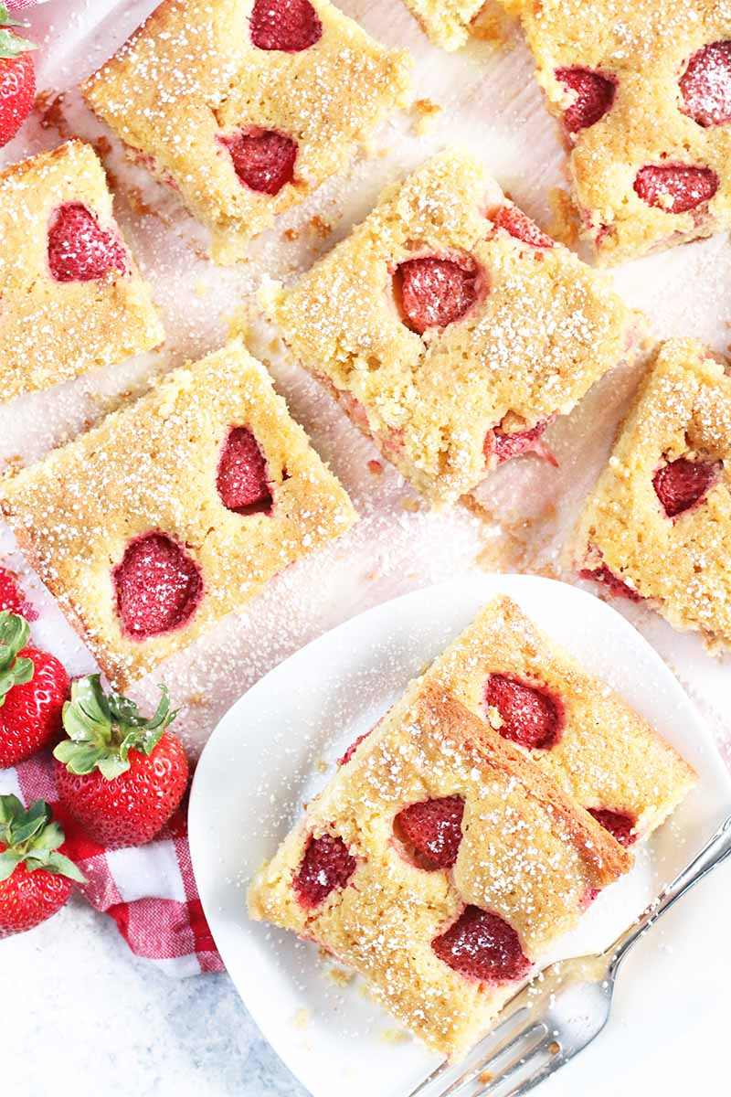 Top-down shot of square slices of strawberry slab cake, with more on a plate to the right with a fork, and scattered whole red berries with green stems to the left.