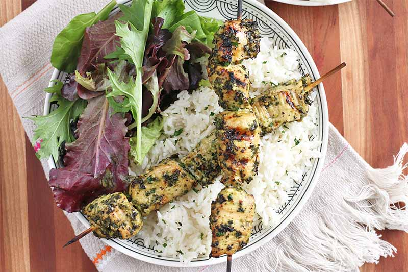 Two grilled chicken skewers on the rim of a white plate of salad greens and white rice, on top of a white folded cloth towel with fringe, on a brown wood table.