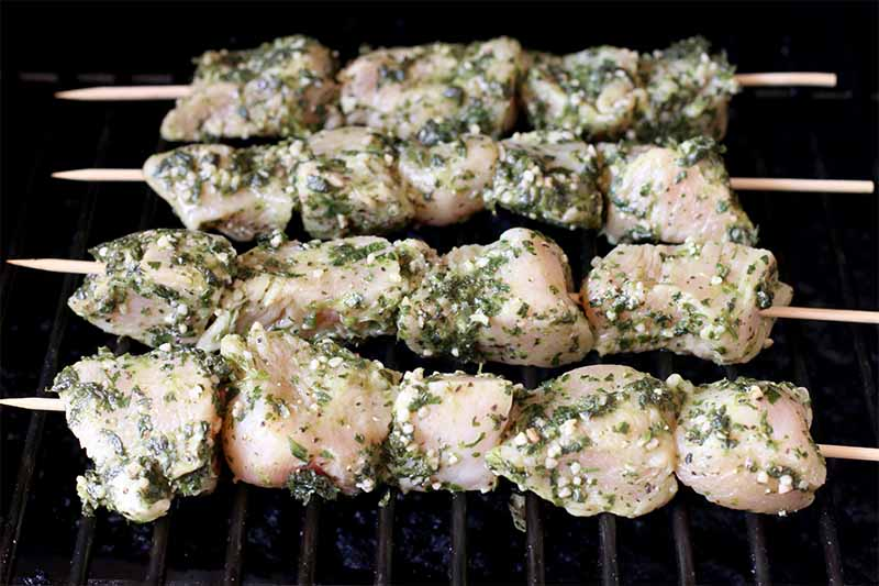 Raw chicken breast covered in an herb marinade, on wooden skewers on the grill.