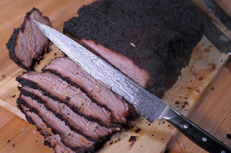 Oblique view of a Japanese Sujihiki knife carving a smoked brisket.