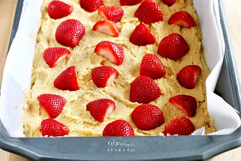 Halved strawberries arranged in rows on top of a thick beige batter in a rectangular metal pan lined with parchment paper.