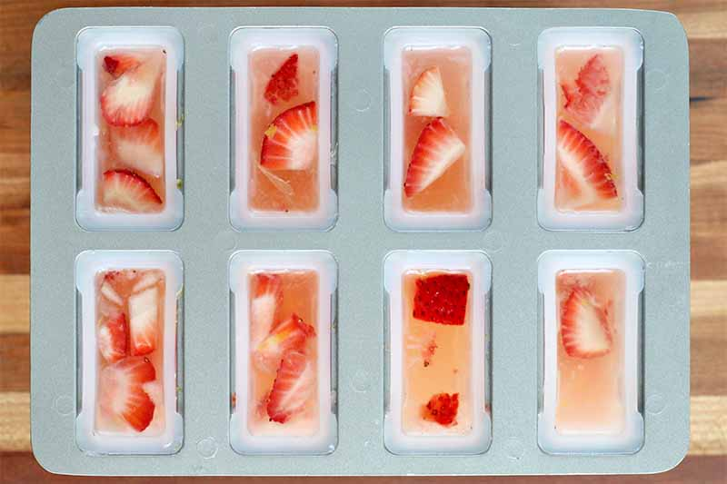 Top-down shot of a gray eight-slot popsicle mold filled with strawberries and lemonade, on a wood surface.