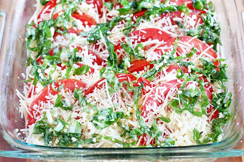 A glass baking dish filled with sliced red tomatoes, chopped herbs, and shredded cheese.