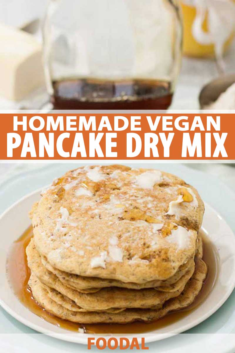 An oblique view of a vegan pancake stack made with a homemade dry mix recipe. A bottle of maple syrup is in the background.