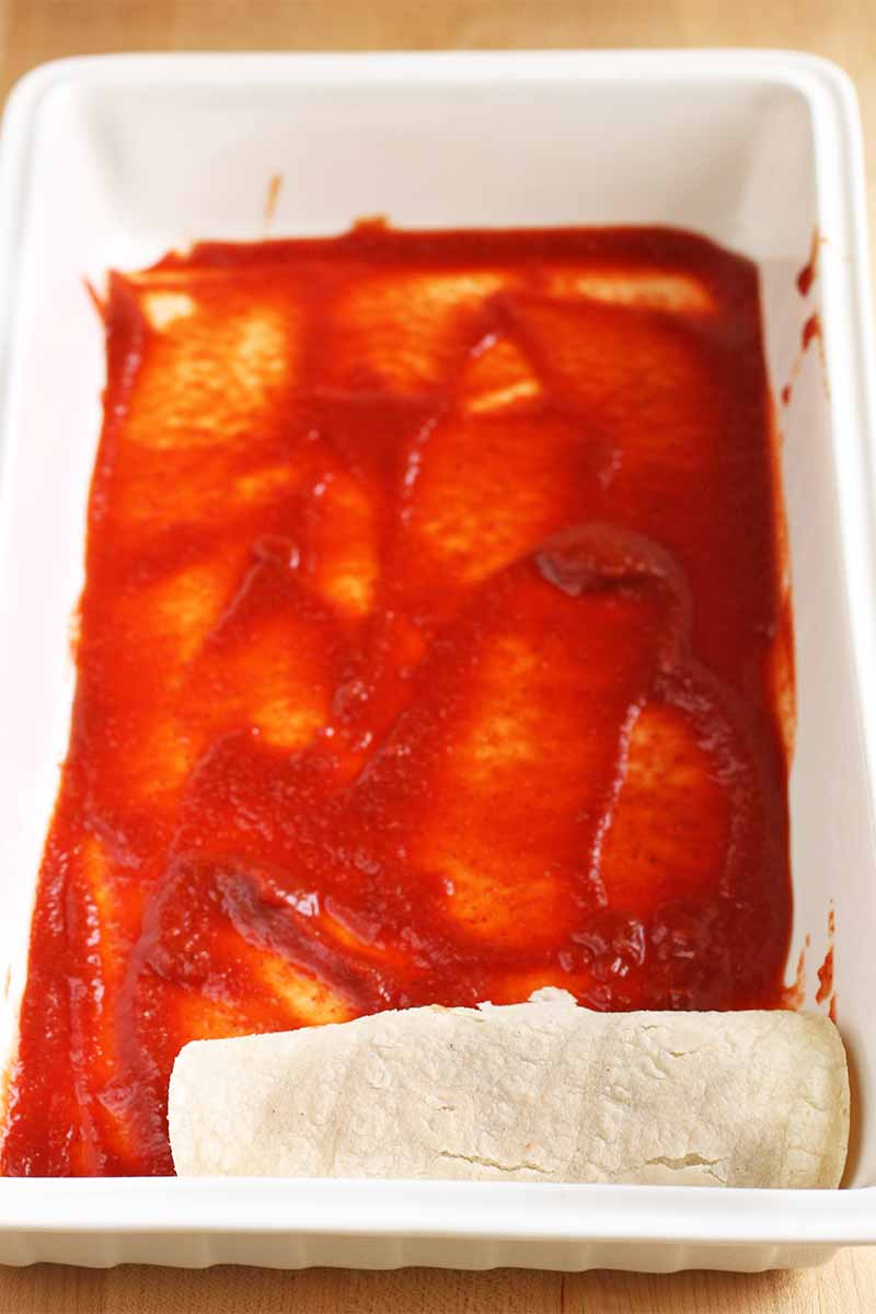 The bottom of a rectangular ceramic baking dish is spread with a red sauce, with a rolled tortilla in one corner, on a beige particleboard background.