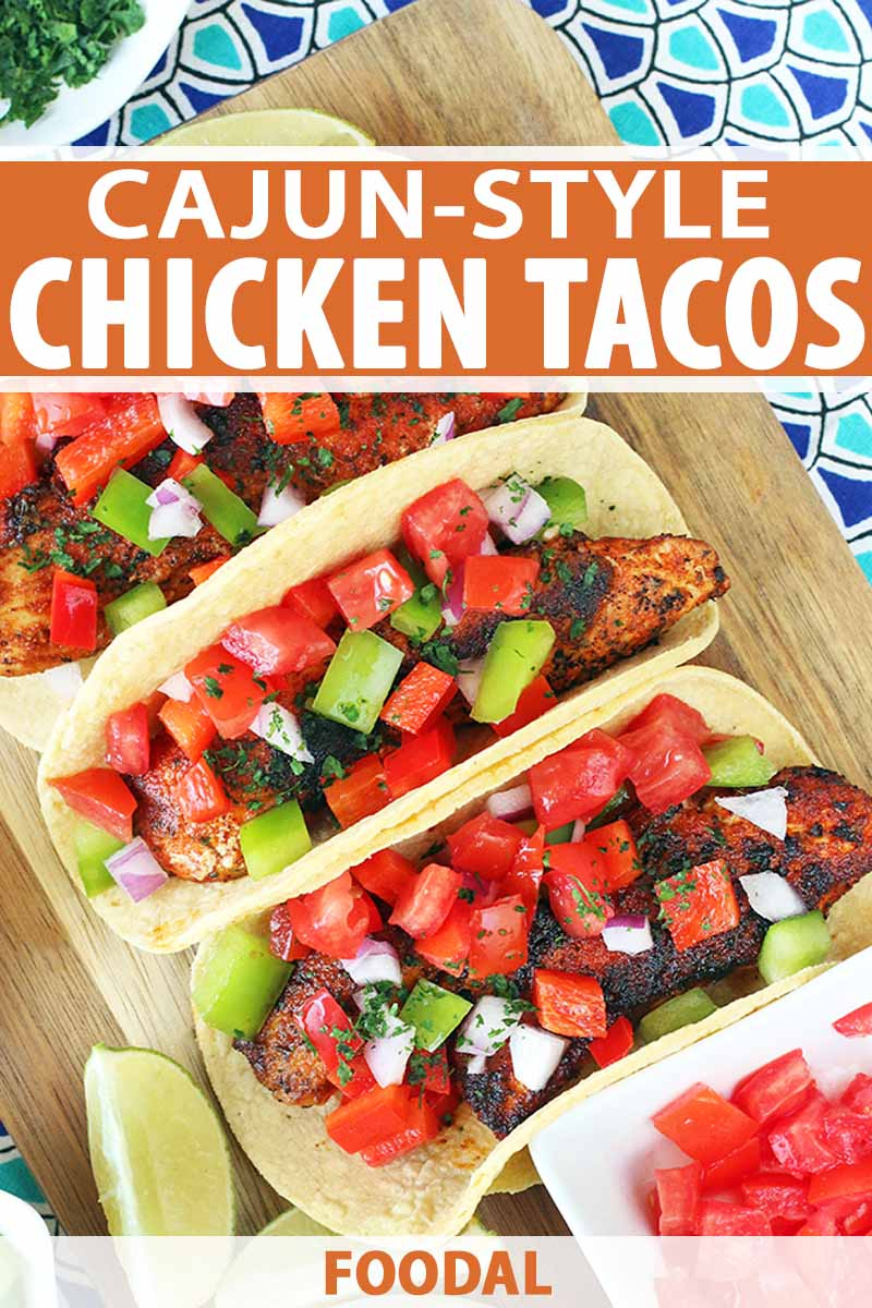 Vertical top-down image of three Cajun chicken tacos topped with chopped vegetables, on a wood cutting board with lemon wedges and a small ceramic dishes of chopped tomatoes and parsley, on a dark and light blue patterned background, with orange and white text.