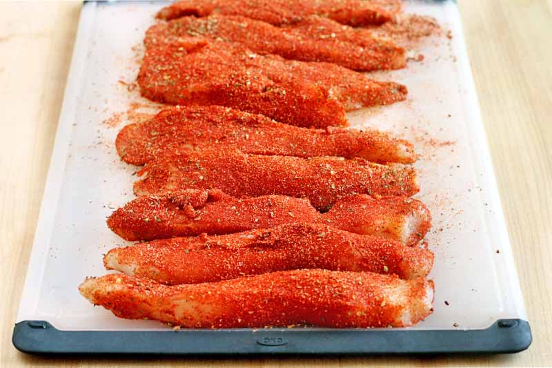 Chicken breast strips are arranged in a row on a black and white plastic cutting board, coated with a red spice mixture, on a beige countertop.