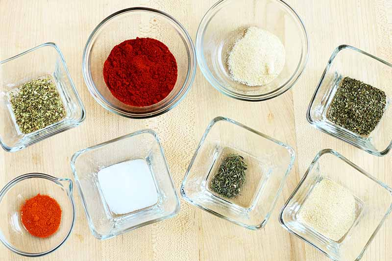 Overhead shot of eight round and square glass bowls of dried herbs and spices, on a beige surface.