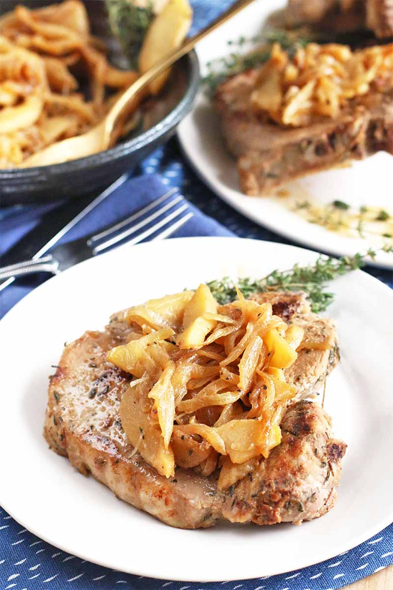 A bone-in pork chop topped with a small pile of caramelized onions and apples is on a white plate with a sprig of fresh rosemary for garnish, with a fork and a blue cloth napkin, and more of both dishes in a gray serving bowl with a gold spoon, and on a white serving platter.
