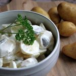Close up of white porcelain bowl full of German potato salad garnished with parsley with raw potatoes in the background.