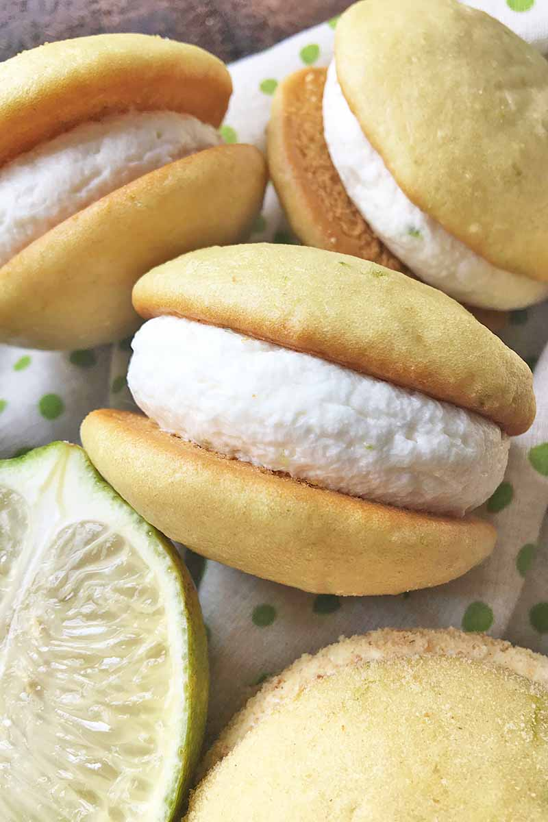 Vertical close-up image of cake rounds filled with white icing next to a slice of lime.