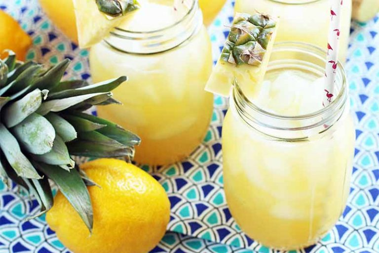 Three glass mason jars of tropical lemonade, with pink and white paper straws, a pineapple top and pieces arranged on the lip of each jar for garnish, and a whole lemon, on a light and dark blue patterned background.