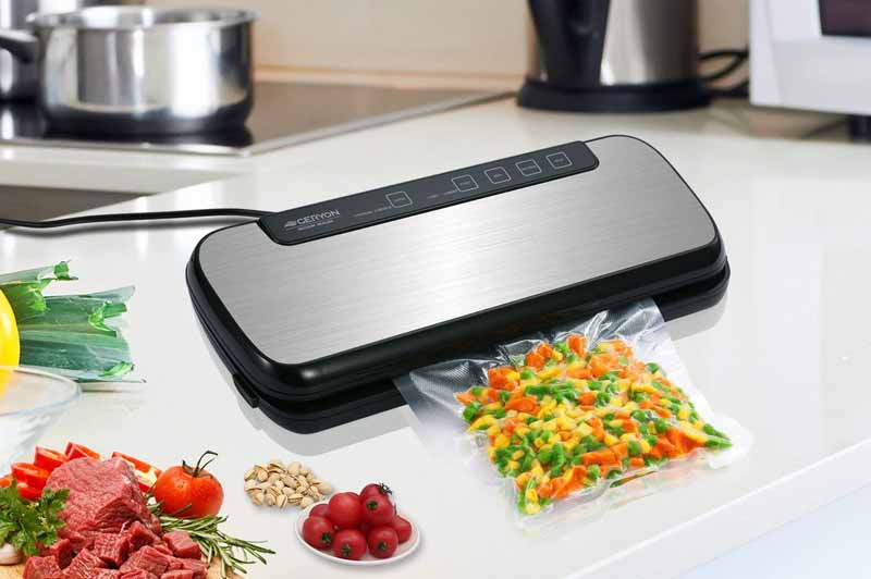 The Geryon E5700 Vacuum Sealer on a white, quartz countertop bagging mixed veggies.