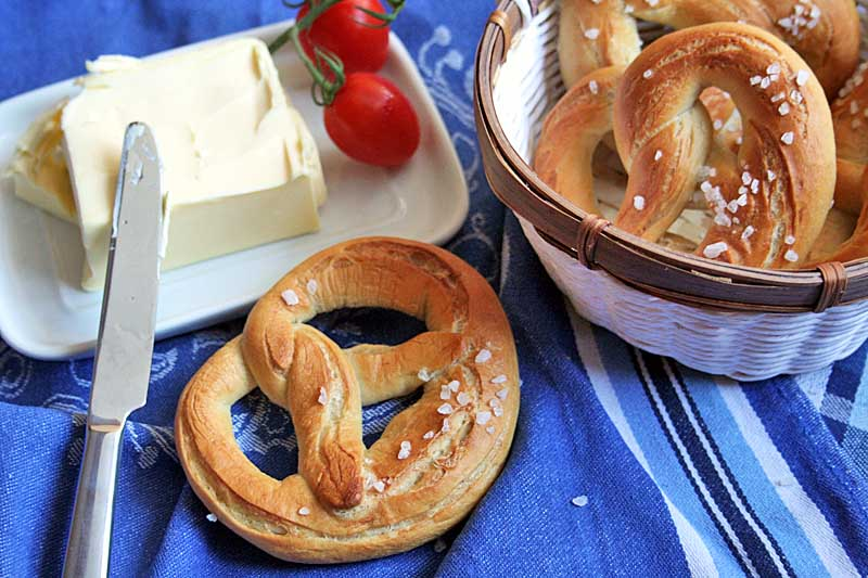 A batch of homemade soft pretzels set up like a still life with a lump of butter, cherry tomatoes, table knife and a white and brown porcelain bowl.