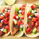 Three Cajun chicken tacos topped with chopped vegetables, on a wood cutting board with small ceramic bowls of garnish and lime wedges.