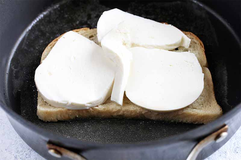 Closeup of a nonstick frying pan with a piece of sourdough bread with large slices of fresh mozzarella on top.