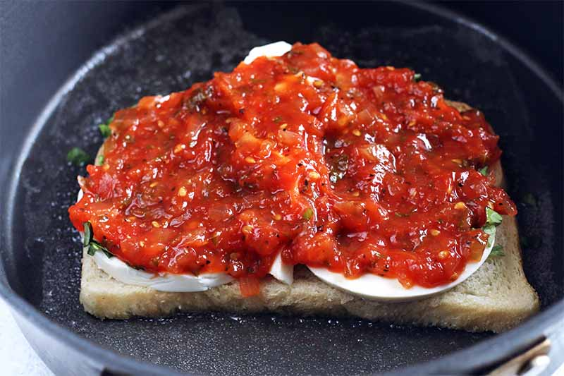 A piece of sourdough bread topped with slices of mozzarella and spread with tomato jam, in a nonstick frying pan.