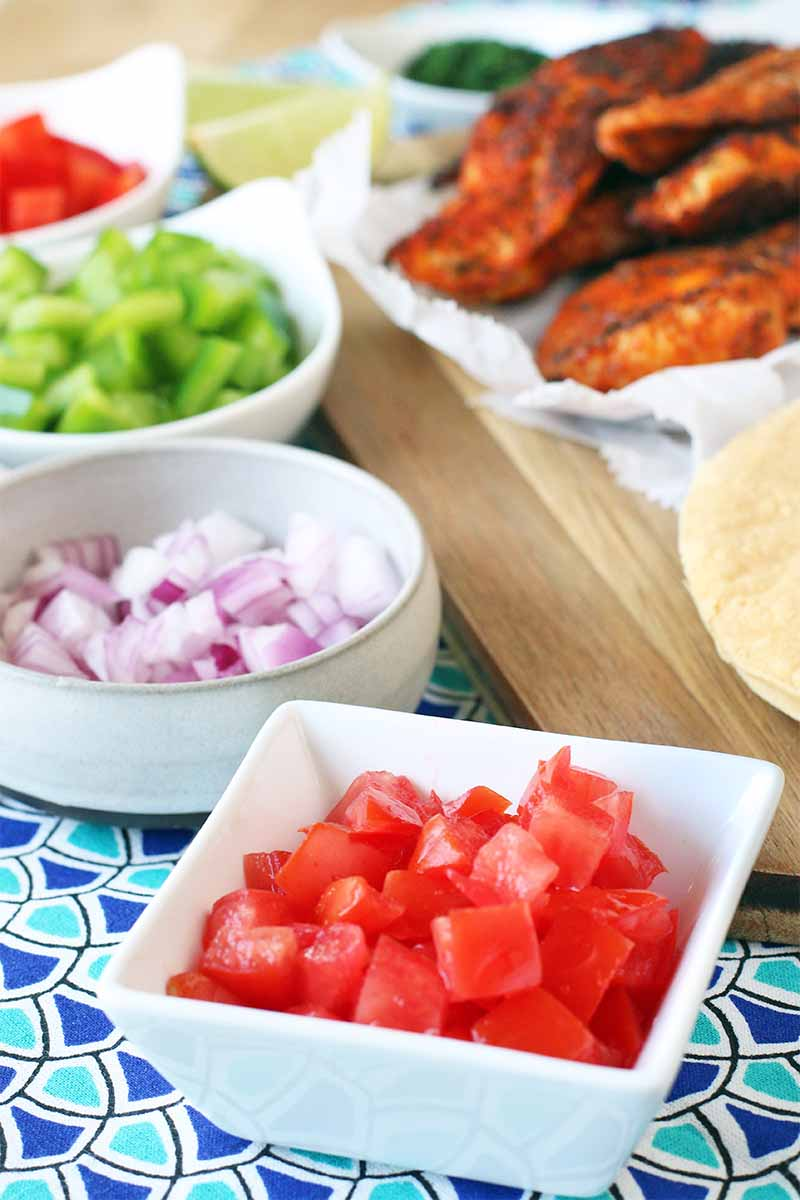 Small ceramic bowls of chopped parsley, red and green bell pepper, purple onion, and tomato, to the left of a cutting board topped with spiced chicken tenders on a piece of parchment, and corn tortillas, on a dark and light blue patterned cloth surface.