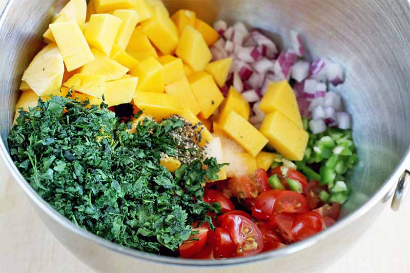 A stainless steel bowl with separate piles of mango chunks, chopped purple onion, chopped jalapeno, chopped grape tomatoes, and minced cilantro at the bottom.
