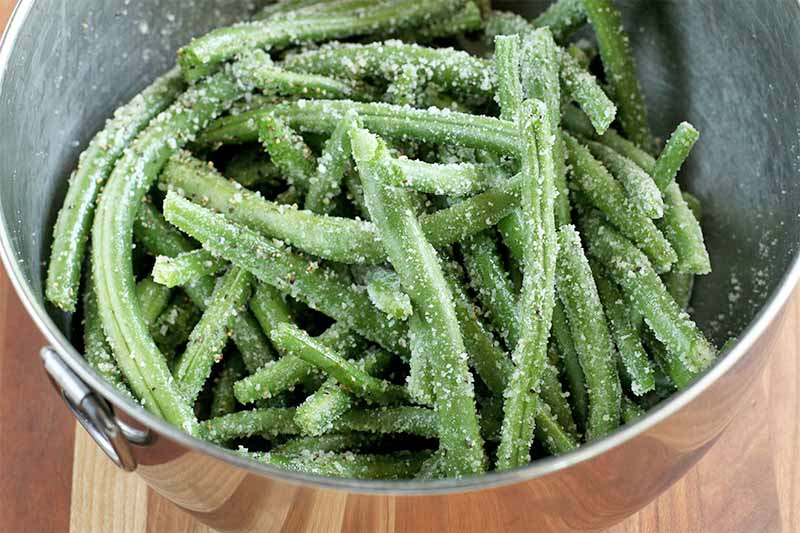 Fresh string beans coated with parmesan cheese, in a stainless steel mixing bowl, on a wood surface.