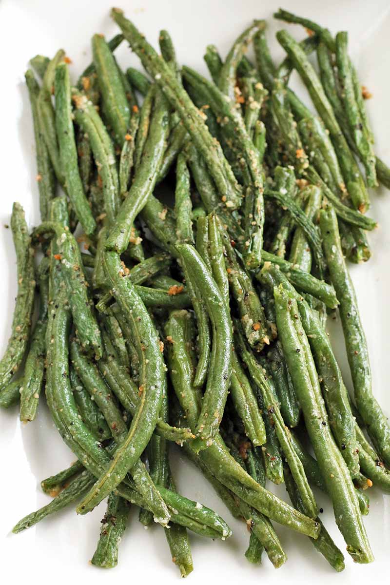 Top-down vertical closeup of a white rectangular dish of roasted green beans, brown in places from cooking, with parmesan cheese, salt, and pepper.