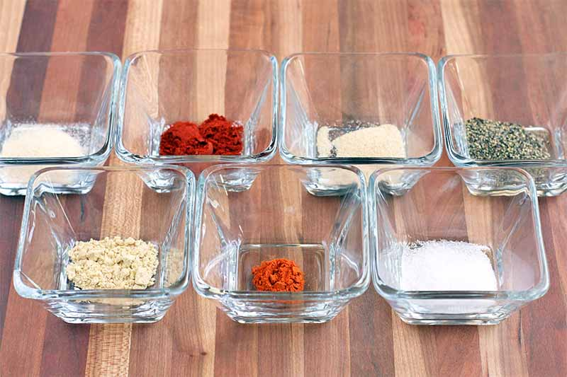Seven small square glass dishes, each containing a different type of ground spice, on a striped wood background.