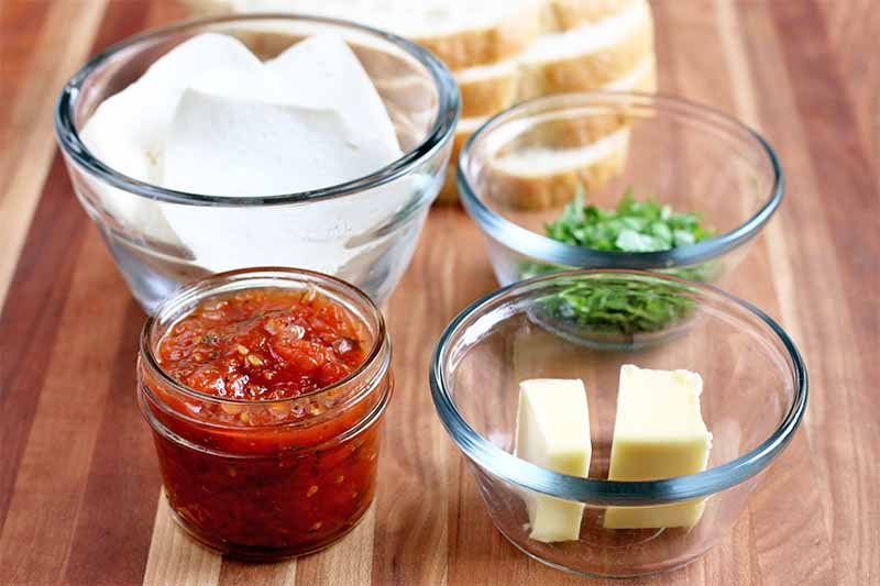 A small glass jar of homemade tomato jam and three glass bowls of sliced fresh mozzarella, chopped basil, and two pieces of butter, with a stack of sliced sourdough bread in the background, on a brown wood surface.