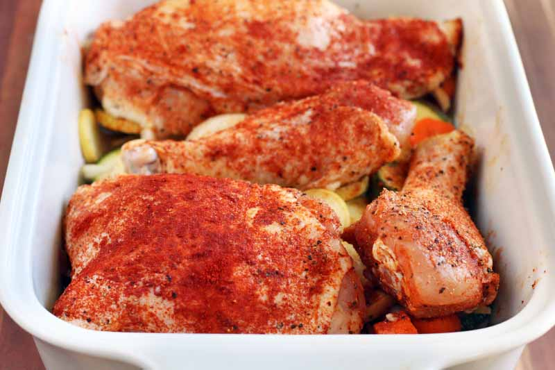 Raw chicken sprinkled with a red spice mixture in a white ceramic baking dish, on top of cut vegetables.