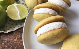 Horizontal image of whoopie pies on a white plate with sliced limes in the background.