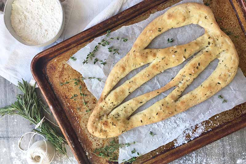 Horizontal image of baked flatbread on a baking sheet with paper underneath.