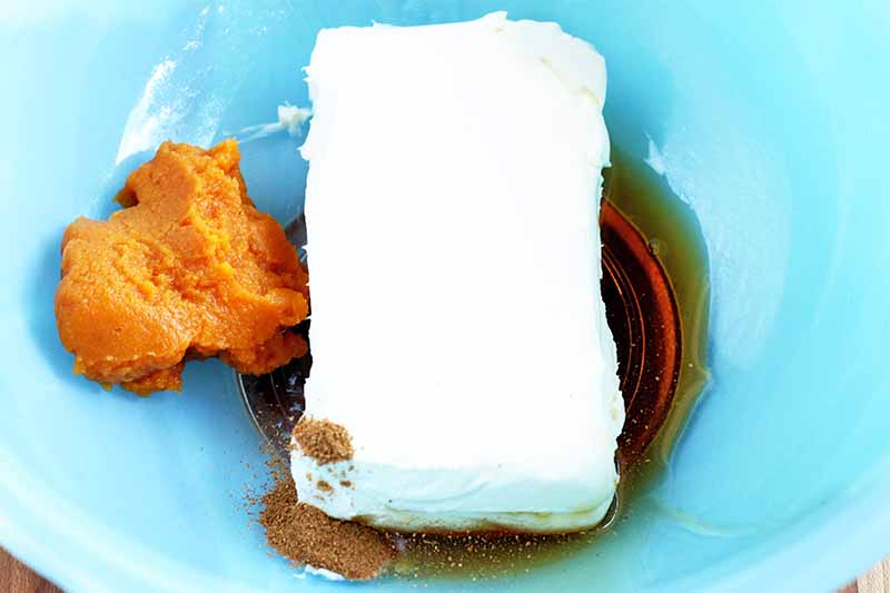 A block of cream cheese is in a blue glass bowl with maple syrup, spices, and a dollop of pumpkin puree.