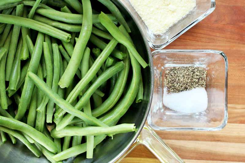 Top-down shot of a stainless steel bowl of raw green beans, and small square glass dishes of grated parmesan cheese, salt and pepper, and cooking oil, on a brown striped wood surface.