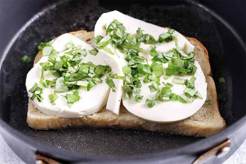 A piece of sourdough bread in a nonstick pan, with slices of fresh mozzarella and chopped basil on top.