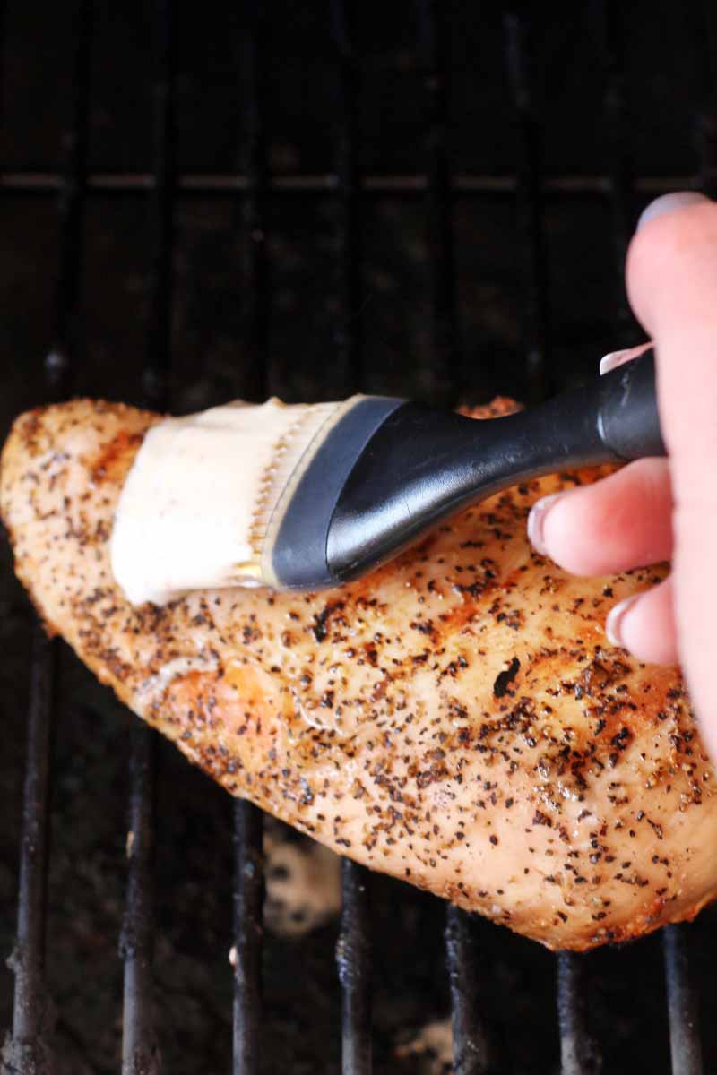 A woman's hand with manicured nails uses a black plastic and silicone brush to spread white barbecue sauce on a spice-rubbed chicken breast on a metal grill grate.