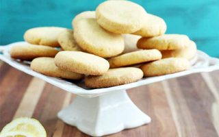 Lemon cookies are arranged on a white ceramic pedestal serving platter, with sliced yellow citrus on a wood surface, with an aqua background.