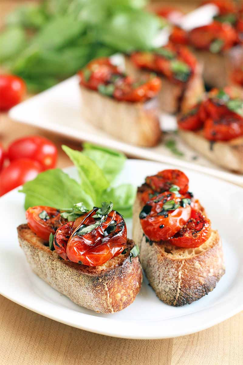 Two pieces of crostini with a balsamic reduction drizzle and basil garnish, on a white plate, with more on a white rectangular serving platter on the background, on a light brown wood surface with scattered grape tomatoes and a bunch of green fresh basil.