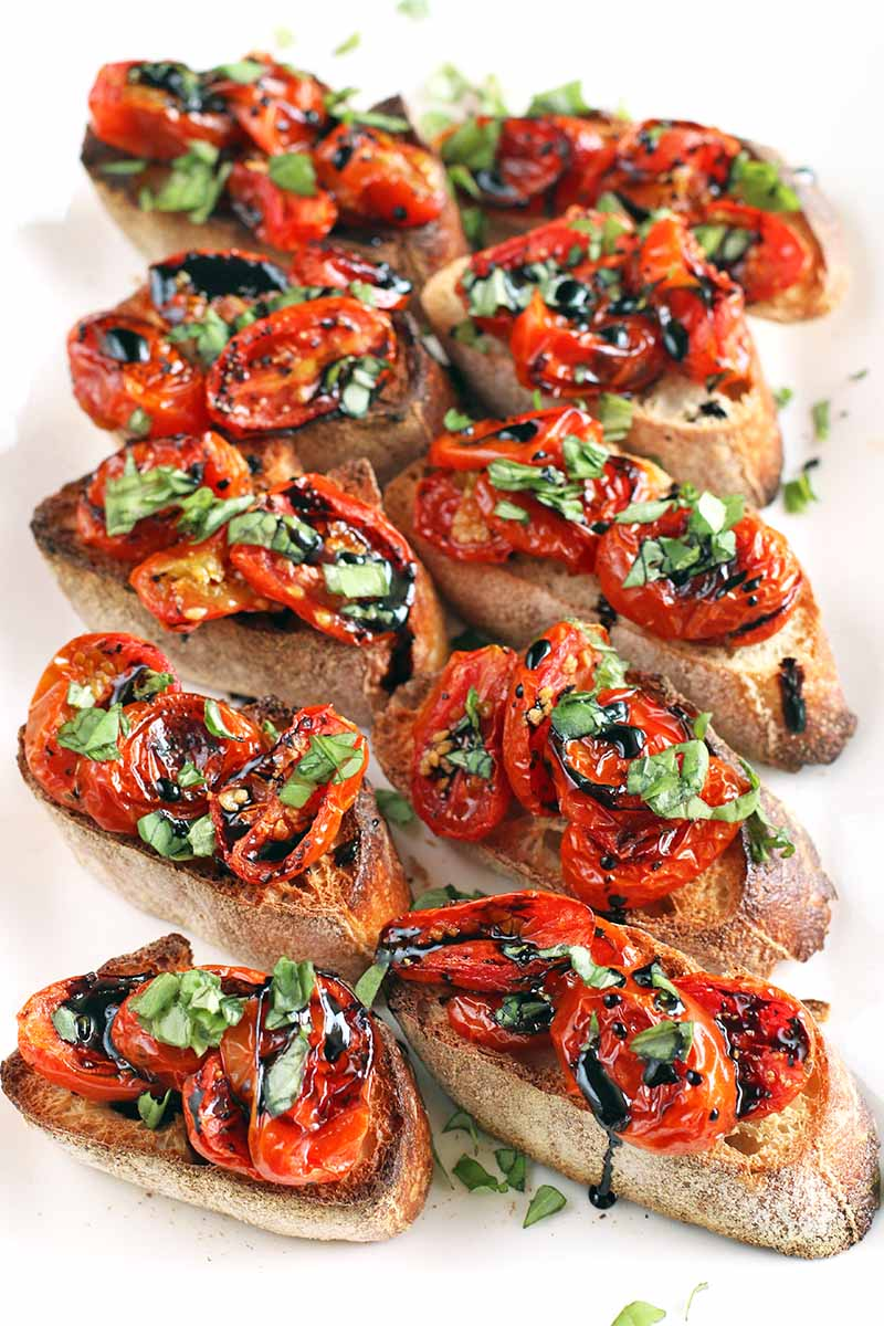 Vertical overhead shot of five rows of two crostini with baguette toast, roasted grape and cherry tomatoes, chopped basil, and balsamic reduction, on a white plate.