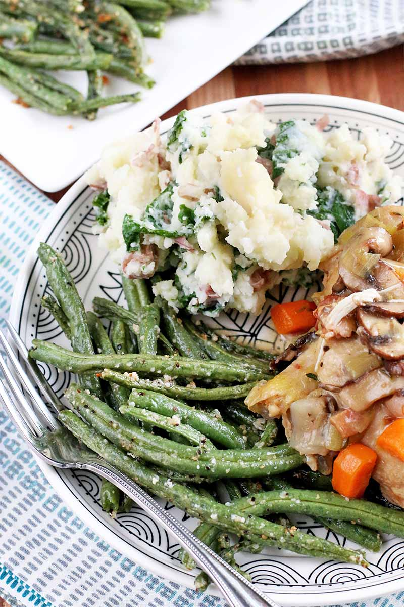 A black and white patterned plate of roasted green beans, mashed potatoes with kale, and chicken with root vegetables, with a fork, on a blue and white cloth with a rectangular white serving platter of vegetables in the background, on a brown wood surface.